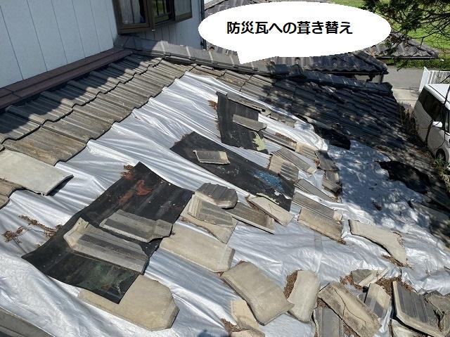 下屋根のセメント瓦屋根が崩れ、銀色のシートが掛けられている