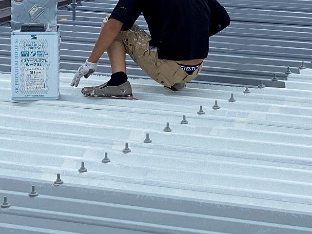 折板屋根にプレミアムルーフを塗布する職人
