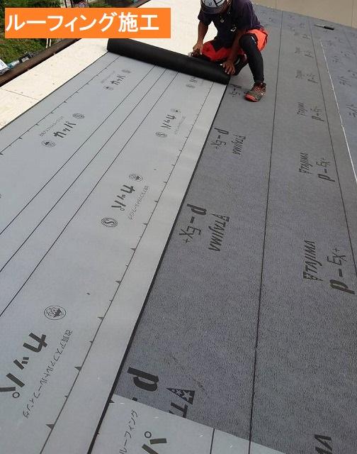 野地板にルーフィングを施工する職人