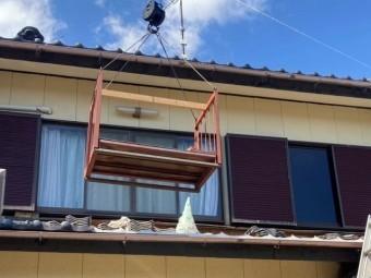 ユニックに鉄籠を吊るし、揚げ降ろしを行っている風景