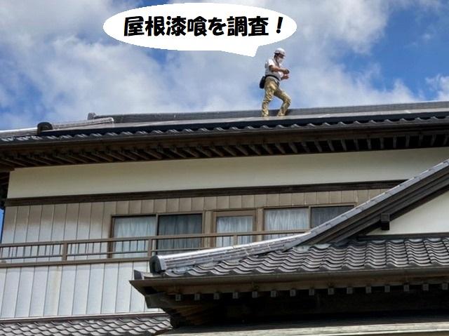 屋根に登り屋根漆喰の調査を行うスタッフ