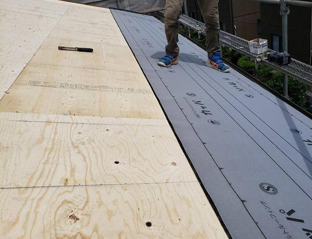 屋根に野地板とルーフィングを貼る職人