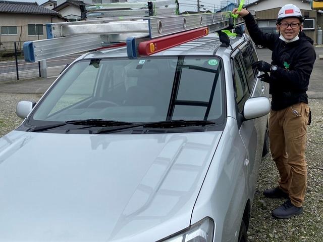 社用車から二連梯子を降ろす準備をするスタッフ