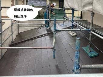 小雨の中で屋根の高圧洗浄を行う塗装職人