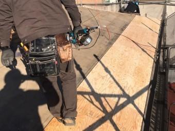 葺き替え工事の為に野地板を増し張りする職人