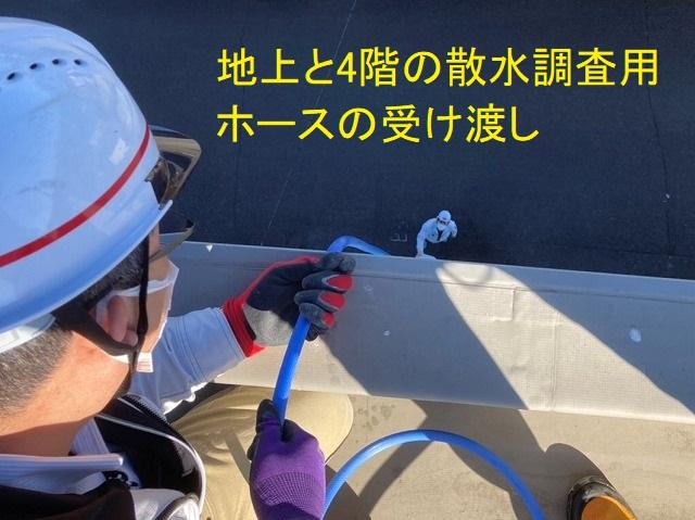 地上と4階の散水調査ホースの受け渡しをするスタッフ