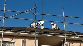 地上から撮影した屋根で作業する二名のスタッフ