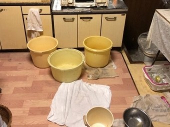 天井からの雨漏りを受ける為に沢山の桶を床におく
