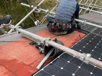 屋根足場で体を支えながら太陽光パネルを撤去する作業員