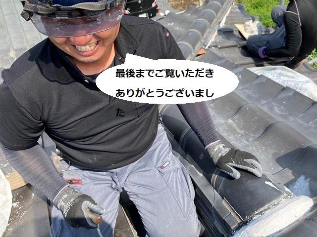 屋根上で笑顔で撮影に協力する職人