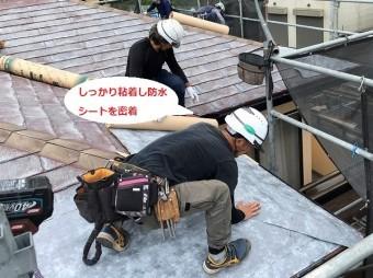 ひたちなか市で施工中の屋根へ粘着式防水紙シートを押さえつけ密着させる