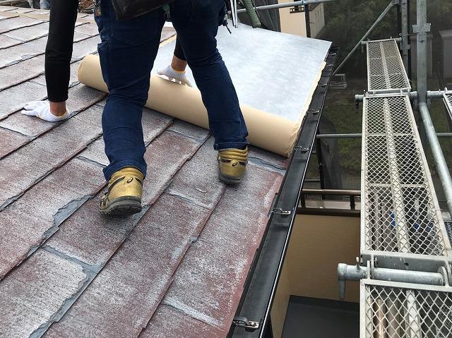 カバー工法を行うパミール屋根材に粘着式防水シートを貼る職人