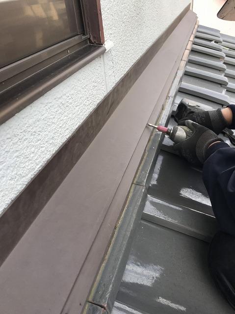 ガルバリウム板金雨押えにステンレススクリュービスを打つ職人