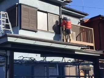 下屋根に立ち竪樋を補修する職人