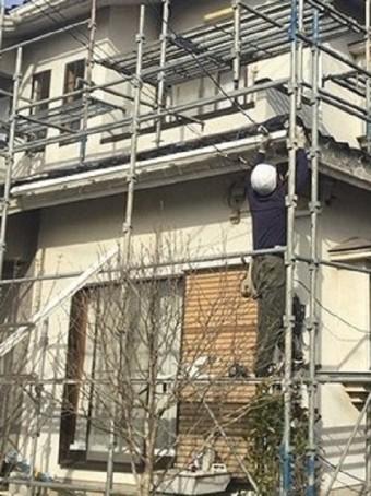 1階の軒に新しい軒樋を施工する職人