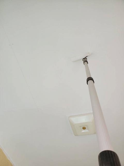 高所棒にローラーをつけ塗布する職人