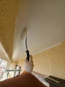 2階の軒天部を塗布する職人