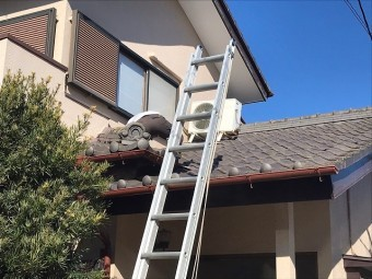 屋根に登り瓦下を覗き込む作業員