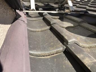 瓦屋根の上にエアコンの室外機の架台が設置されている