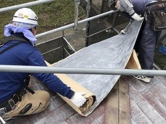 ひたちなか市で粘着式防水シートを使用したパミールへのカバー工法で粘着式防水シートを2人がかりでコーナー部を貼る屋根職人