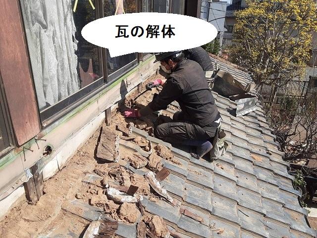 壁際の瓦を解体する職人