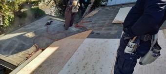 古い防水シートの上から12㎜の構造用合板を施工する職人
