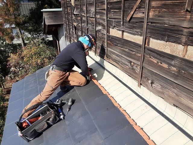 屋根上で踏ん張りながら防災瓦を施工する職人