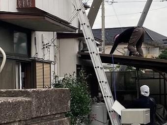 自転車小屋の屋根をつたう職人