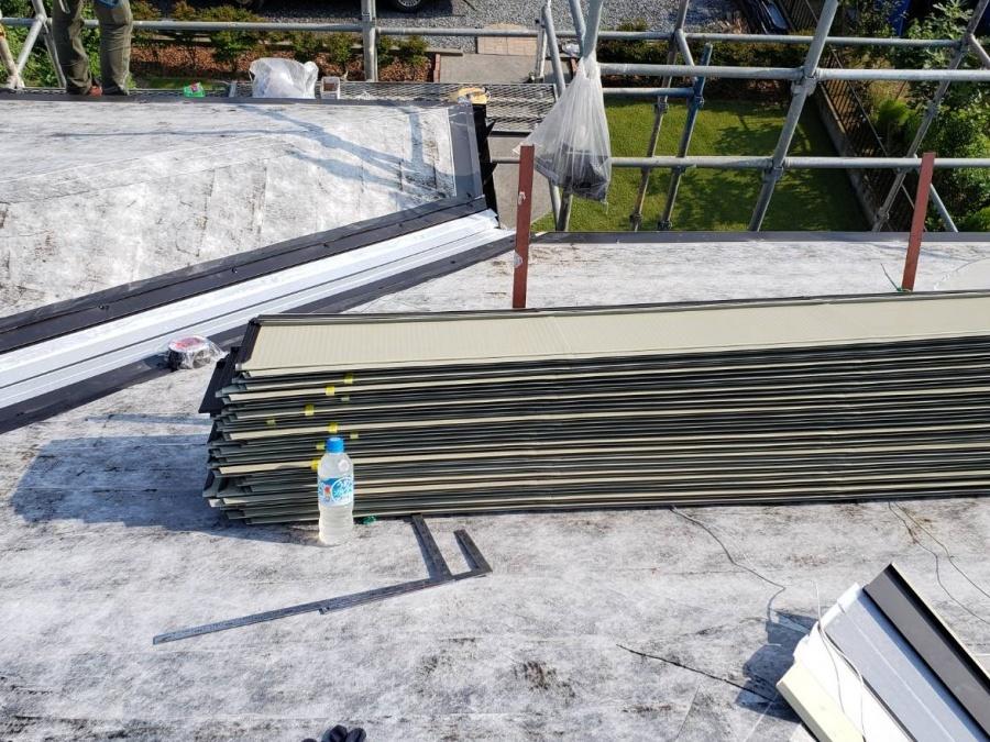 屋根の上に資材止めされて置かれた定尺金属屋根材