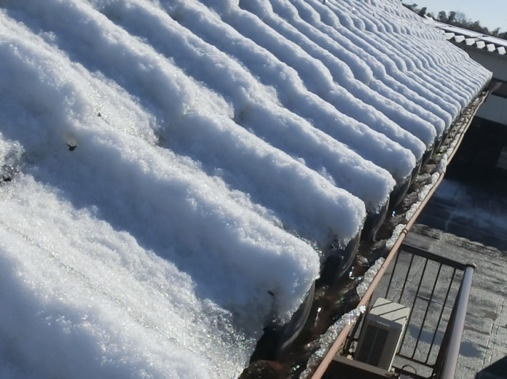 屋根に積雪し軒樋に溶けた雪が溜まっている