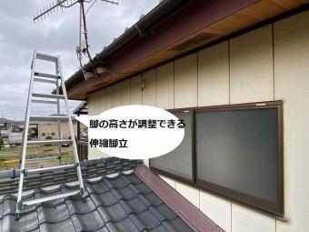 伸縮脚立を下屋根の棟にまたがせて掛ける