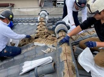 三名の職人が連携して棟瓦を解体してガラ袋に入れていく