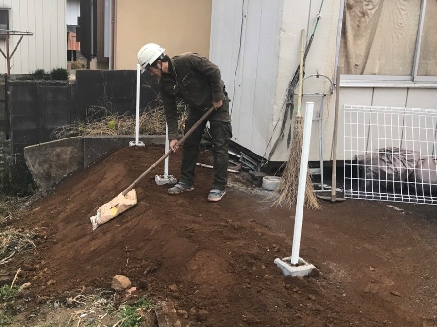 盛り土を行い、道具を使用して土台を叩き固める職人