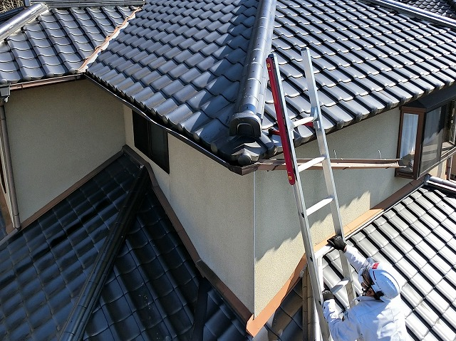 梯子を軒先に架け、破損雨樋を目指すスタッフ