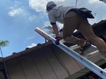 屋根瓦の軒先にハシゴを掛け屋根に登るスタッフ