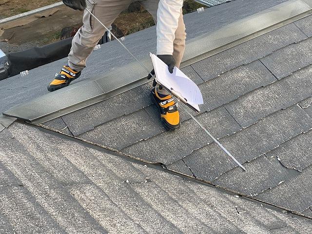 コロニアルネオが葺かれた複合屋根を計測するスタッフ