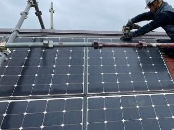 急勾配屋根で太陽光パネルを撤去する作業員