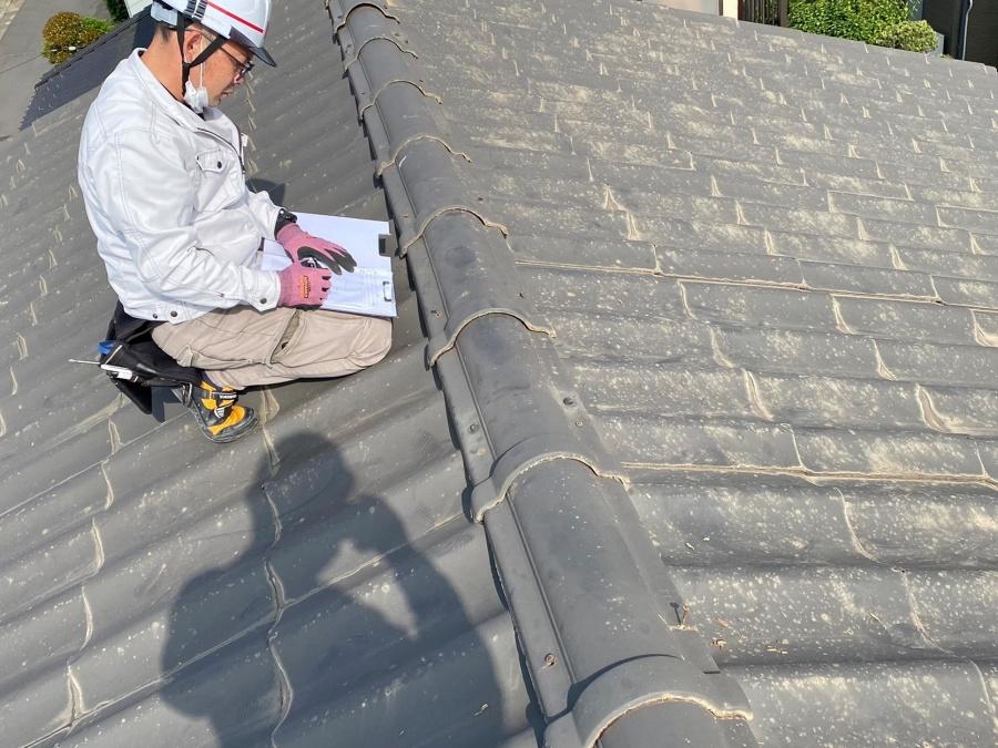 屋根に膝をつき、屋根の状態を手書き図面に書き込むスタッフ