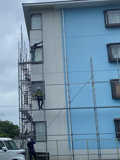四階建てマンションンに足場を架設する職人