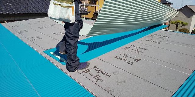新しい波トタンを施工する為トタンを運ぶ職人