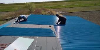 新しい波トタンを施工する二人の職人