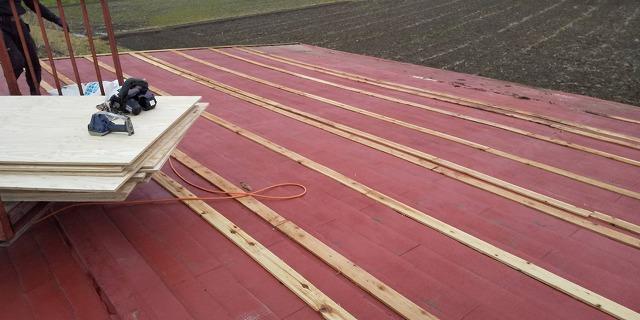 被せ葺きを行う為下地を補強する為野地板を玉掛けで荷揚げ