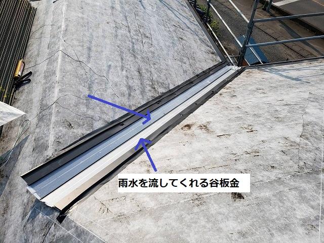白い防水シートの上から雨水を流してくれる谷板金を施工