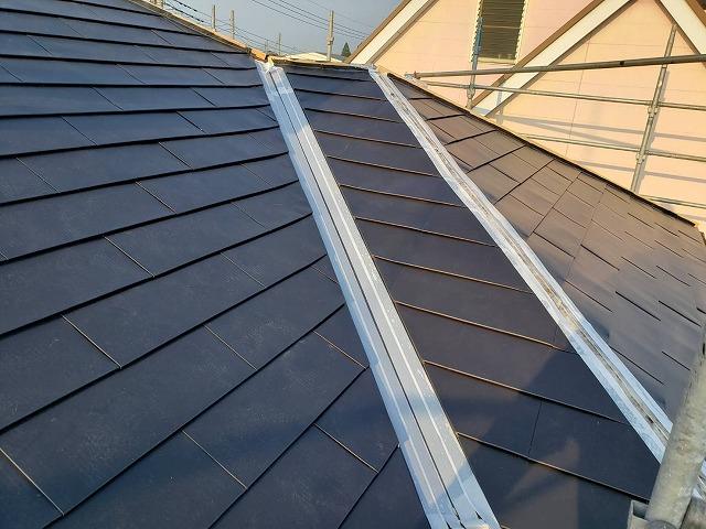 屋根に重ね葺きを行っている途中の谷部と棟部
