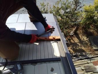 切断加工した瓦を、袖瓦に固定する職人