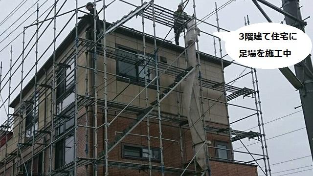 水戸市の3階建て住宅に足場を組む2人の職人
