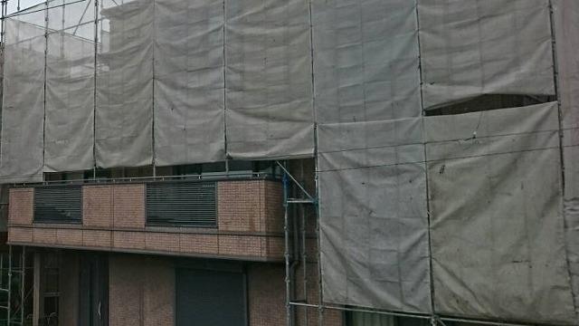 水戸市の3階建て住宅に養生ネットをかけた様子
