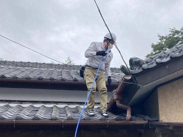 入母屋玄関に登り、雨漏り箇所を特定する為の散水調査を行うスタッフ