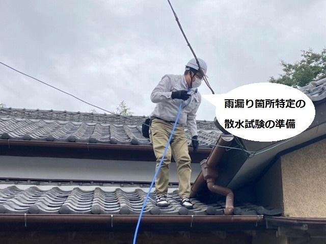散水調査を行うために屋根上にホースを伸ばす調査スタッフ