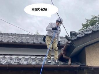 屋根に登り散水をして雨漏り試験を行うスタッフ